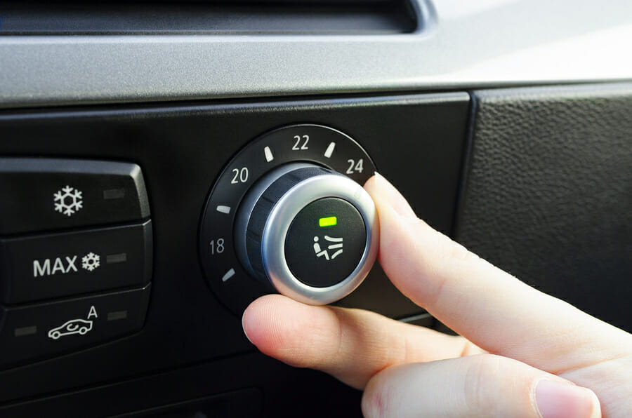 Human hand tuning car climate control system setting the temperature